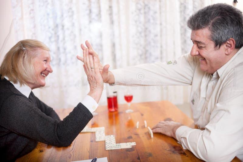 Det lyckliga höga folket i avgånghemmet som spelar dominobricka, spelar fotografering för bildbyråer