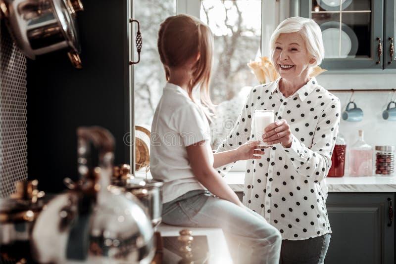 Det lyckliga höga kvinnaanseendet i det moderna kök- och rymmaexponeringsglaset av mjölkar royaltyfri bild