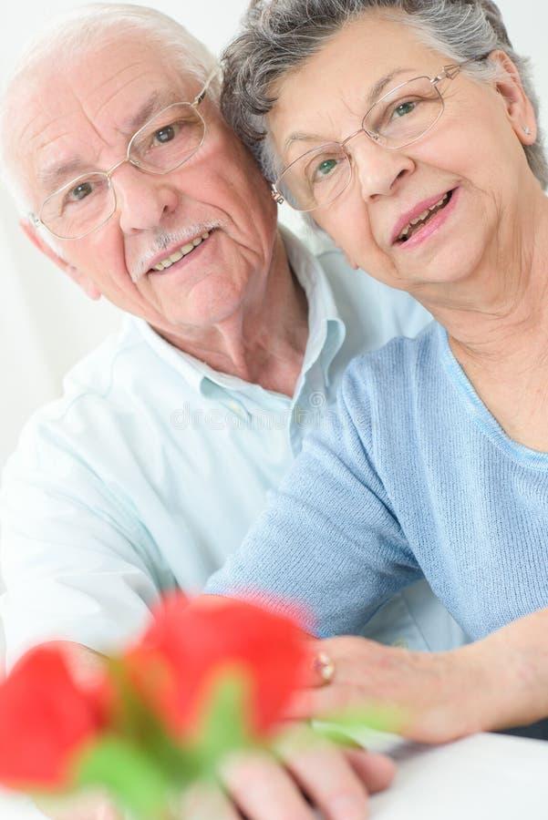 Det lyckliga höga paret vänder mot den äldre den förälskade mannen och kvinnan royaltyfri foto