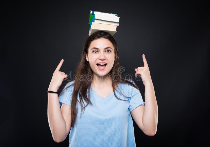 Det lyckliga innehavet för den unga kvinnan bokar på hennes huvud royaltyfria foton