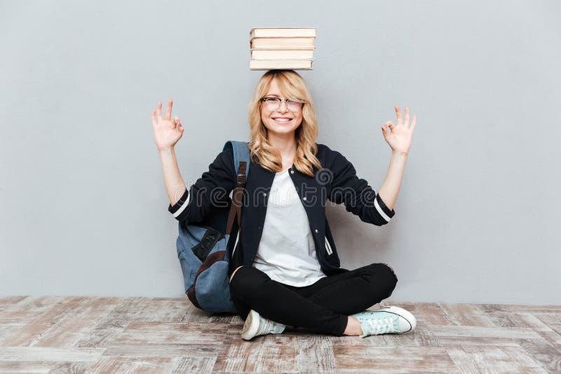 Det lyckliga innehavet för studenten för den unga kvinnan bokar på huvudet arkivbilder