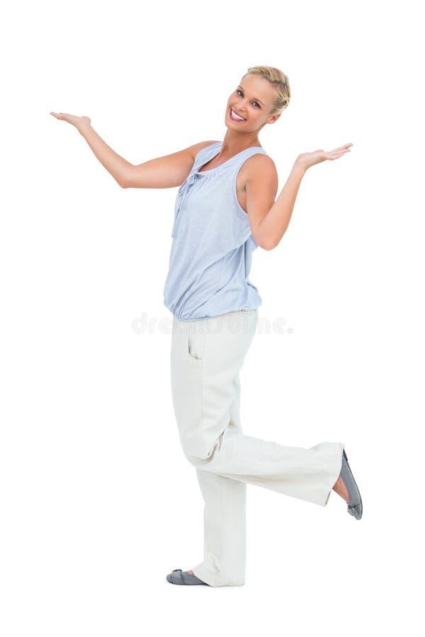 Det lyckliga kvinnaanseendet med händer up och lägger benen på ryggen lyftt arkivfoton