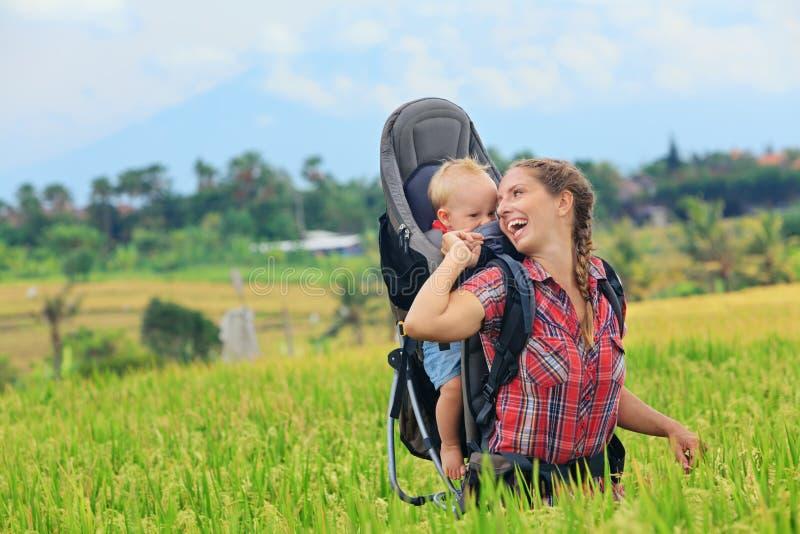 Det lyckliga kvinnahållbarnet i ryggsäck behandla som ett barn bäraren royaltyfri fotografi