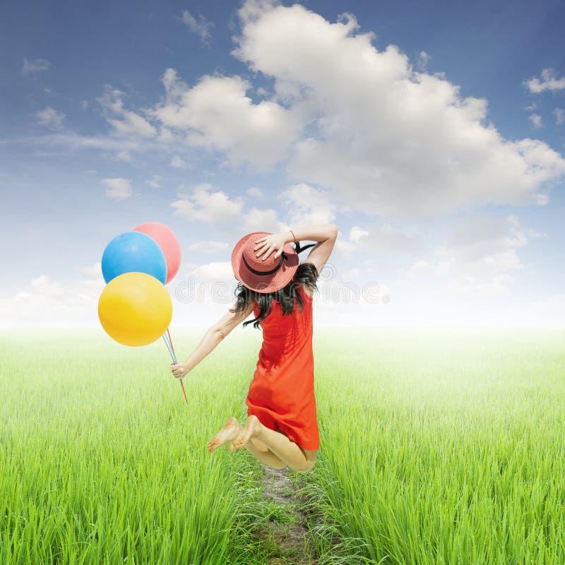 Det lyckliga kvinnainnehavet sväller i gul risfält- och molnhimmel arkivbild