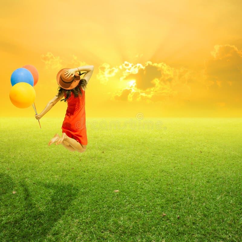 Det lyckliga kvinnainnehavet sväller och banhoppningen på gräsfält och solar fotografering för bildbyråer