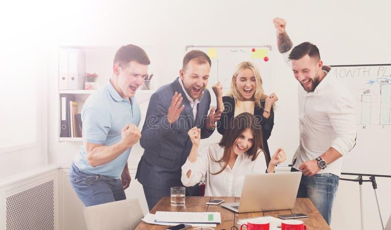 Det lyckliga laget för affärsfolk firar framgång i kontoret royaltyfri fotografi