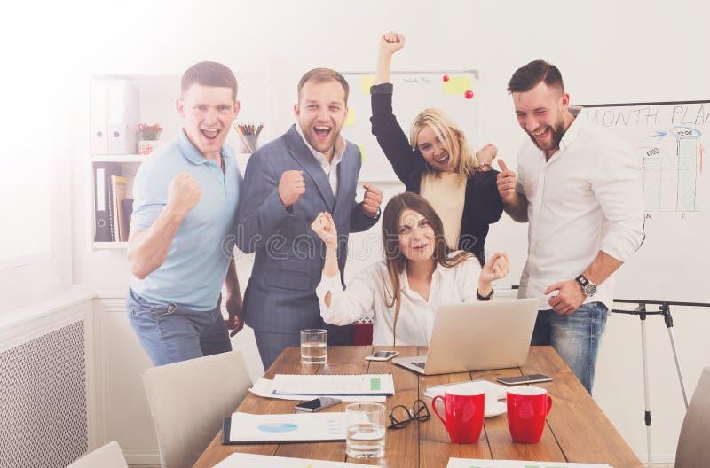 Det lyckliga laget för affärsfolk firar framgång i kontoret arkivfoto