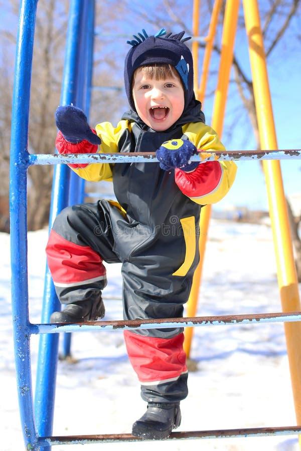 Det lyckliga le barnet i overall spelar på klättrare i vinter arkivfoto