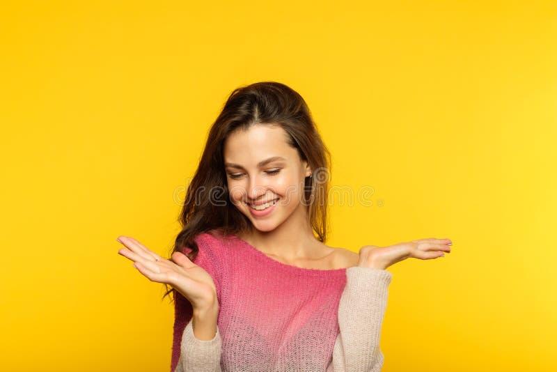 Det lyckliga le kvinnainnehavet räcker jämförelse royaltyfria foton