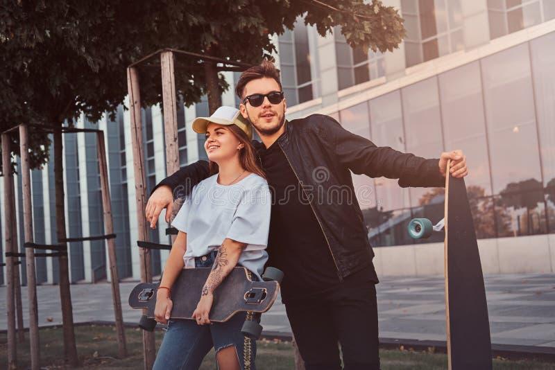 Det lyckliga le paret st?r p? sommargatan med deras longboards arkivbild