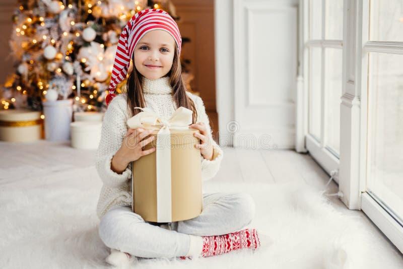 Det lyckliga lilla småbarnet bär den vit stack tröjan rymmer gåvan arkivfoto