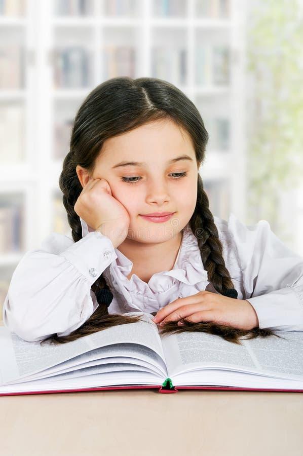Det lyckliga liten flickabarnet läser boken inomhus arkivfoton