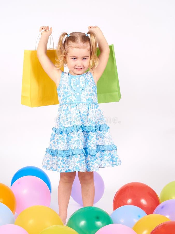 Det lyckliga liten flickainnehav upp shopping hänger lös bags flickan som rymmer little shopping royaltyfri fotografi