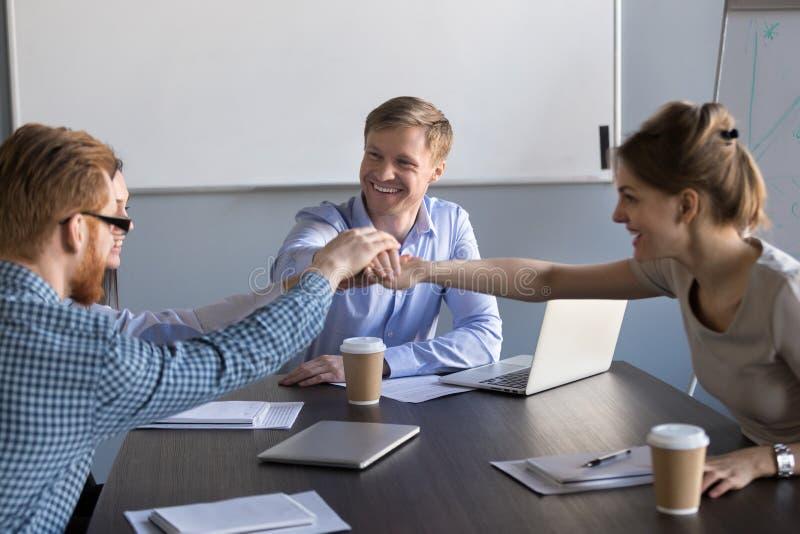 Det lyckliga motiverade affärslagfolket sammanfogar händer tillsammans på mötet royaltyfri bild