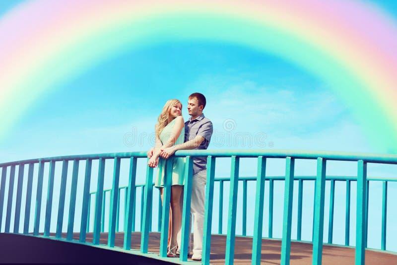 Det lyckliga nätta unga älska paret står på bron royaltyfria foton