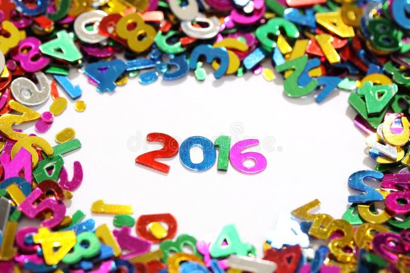 Det lyckliga nya året 2016 från mousserar färgrikt blänker nummer på vit bakgrund och runt om andra nummer royaltyfria foton