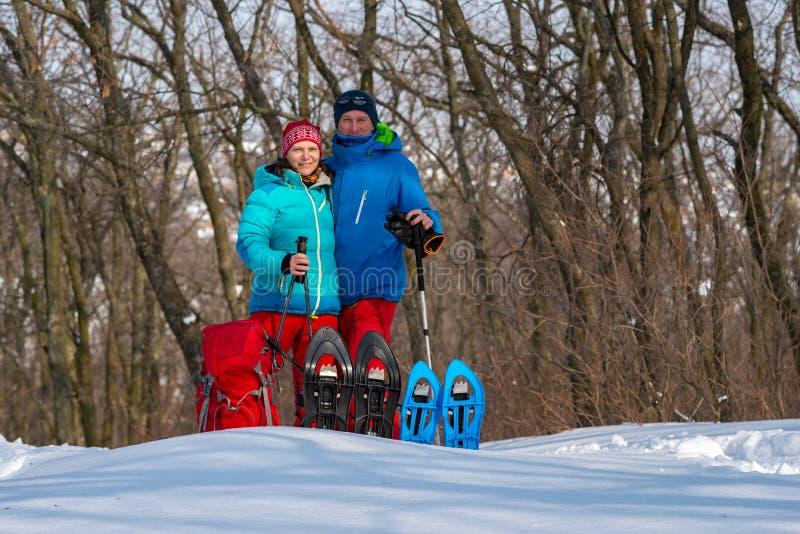 Det lyckliga paret av lycksökare står och att krama, i en vinterskog royaltyfria bilder