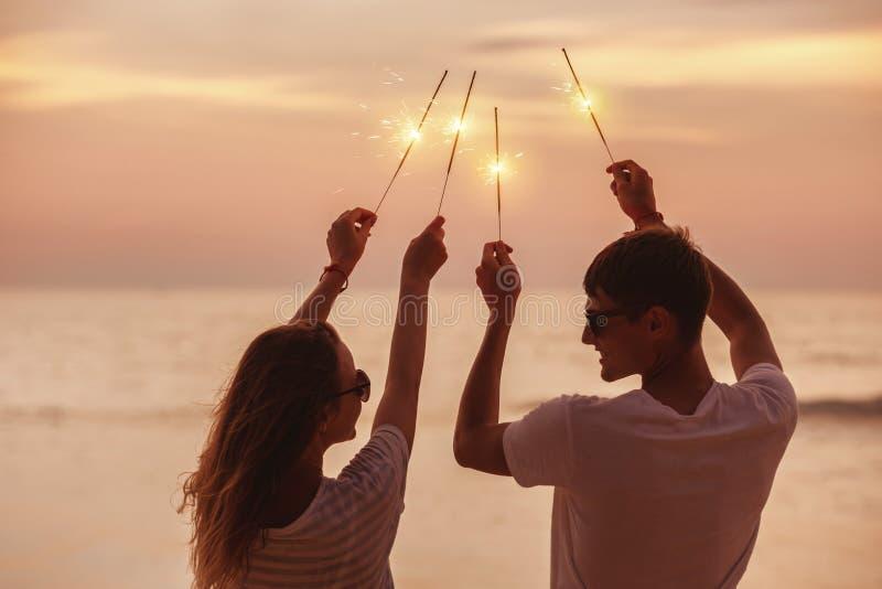 Det lyckliga paret firar solnedgång med tomtebloss royaltyfri fotografi