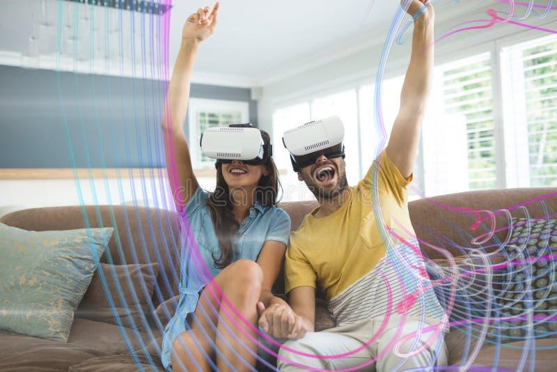 Det lyckliga paret i VR-hörlurar med mikrofon som ser till ljus, har kontakt arkivbild