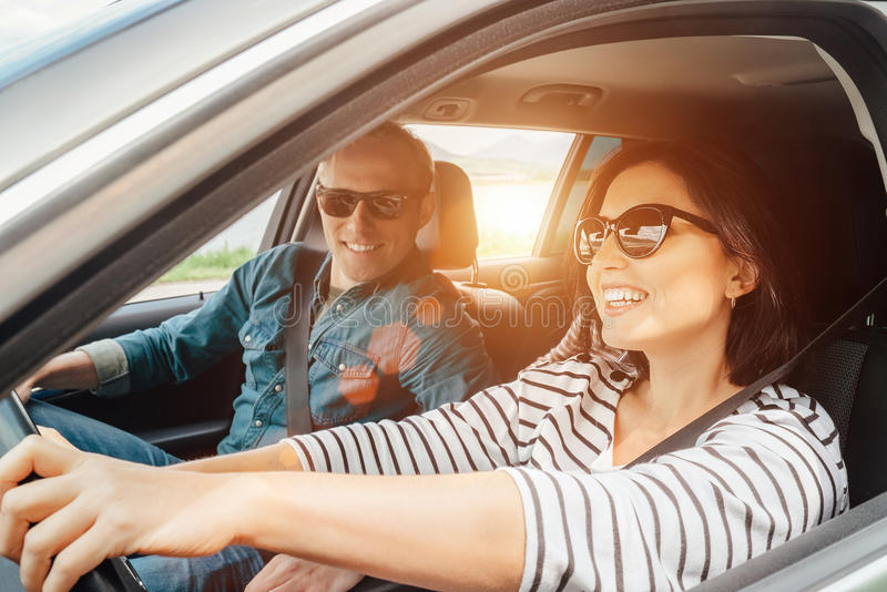 Det lyckliga paret passerar bilen royaltyfri foto
