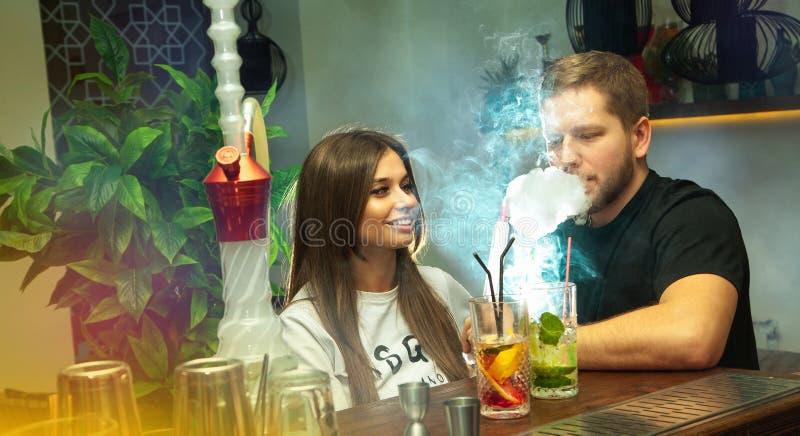 Det lyckliga paret röker shisha- och drinkcoctailar arkivbild