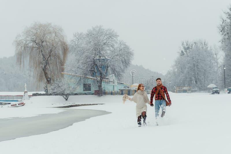 Det lyckliga paret rymmer händer och spring längs ängen som täckas med snö Hus i skogen i vinter arkivfoto
