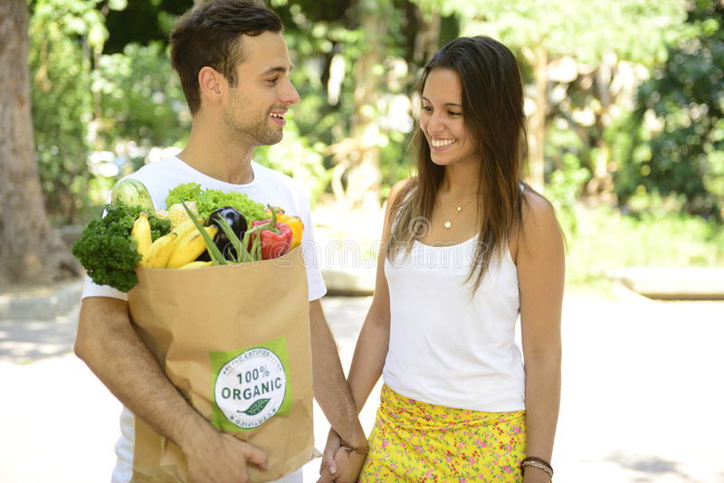 Det lyckliga paret som bär en pappers- påse för återanvändning av organisk grönsakans, bär frukt mycket. arkivbilder