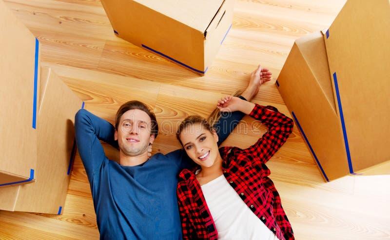 Det lyckliga paret som ligger på golvet i nytt hem med cordboard, boxas omkring royaltyfri foto