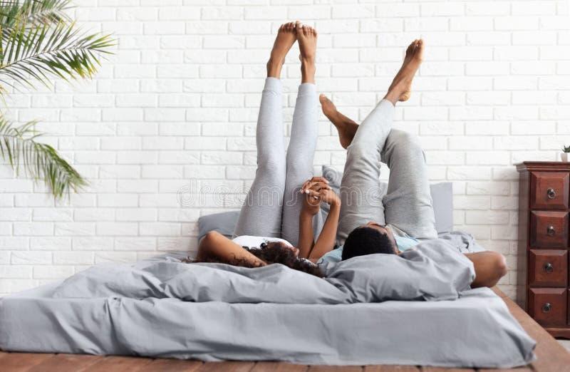Det lyckliga paret som ligger på hemmastatt lyfta för säng, lägger benen på ryggen upp royaltyfria foton