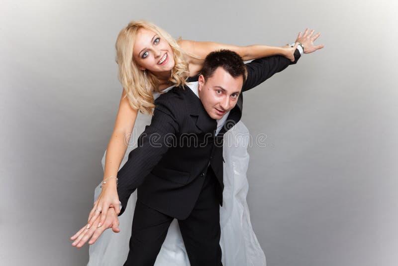 Det lyckliga paret som tycker om att flyga, kvinnlig mans på, tillbaka royaltyfria bilder