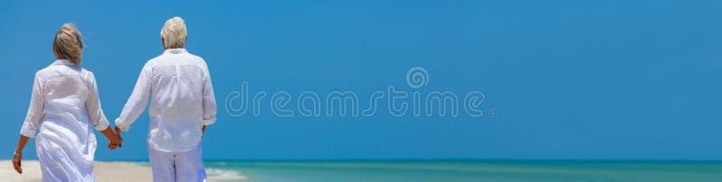 Det lyckliga pensionerade höga paret som går innehavet, räcker strandpanorama arkivbilder