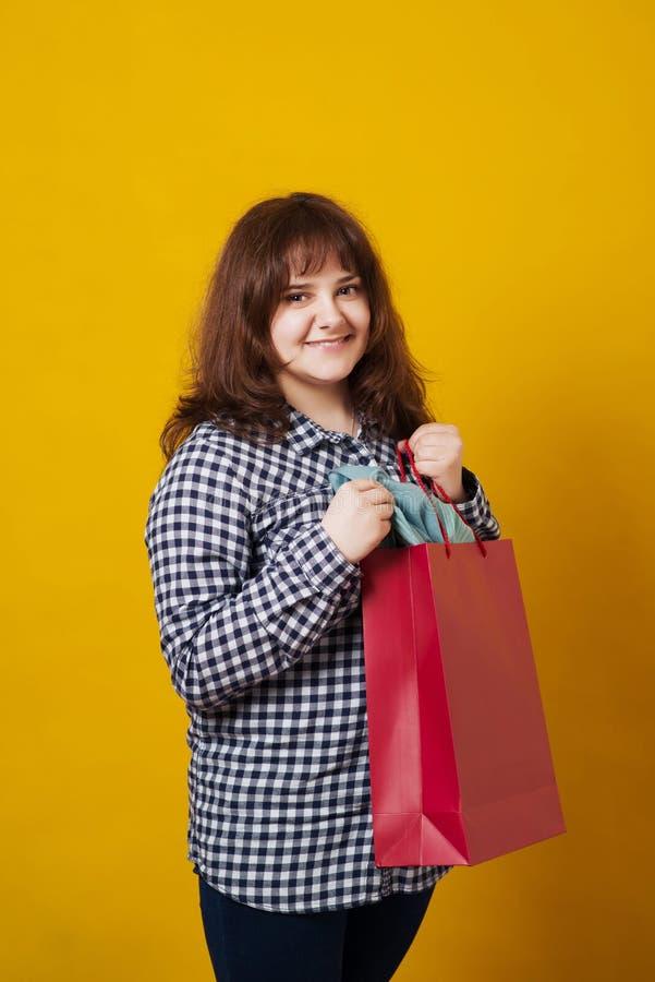 Det lyckliga plus-storleksanpassade kvinnainnehavet färgade shoppingpåsar över gul bakgrund fotografering för bildbyråer