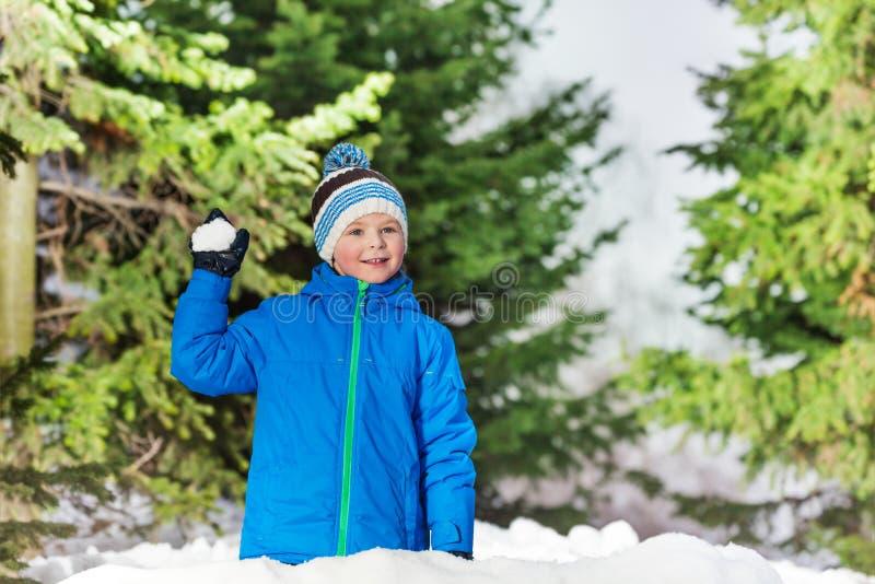 Det lyckliga pojkekastet kastar snöboll i parkera royaltyfria foton