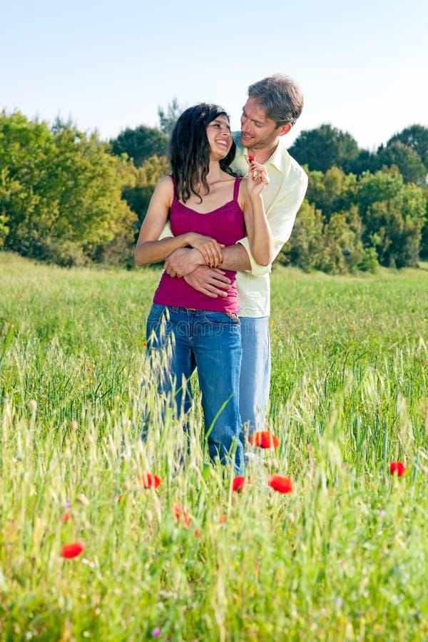 Det lyckliga romantiska barnet kopplar ihop i ett vallmofält royaltyfria foton