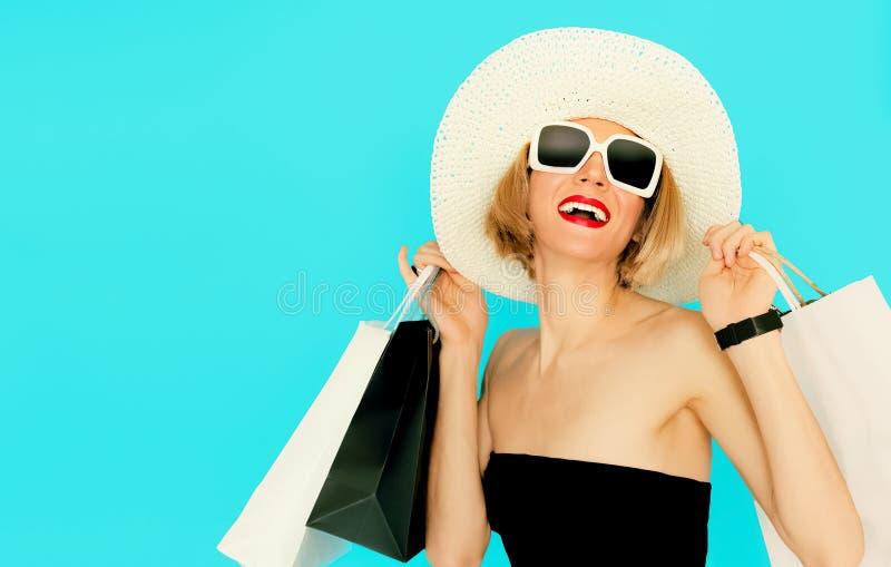 Det lyckliga shoppingkvinnainnehavet hänger löst på blå bakgrund royaltyfri bild