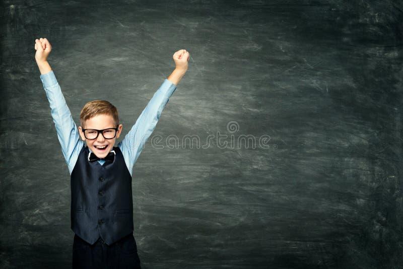Det lyckliga skolbarnet lyftte upp armar, den smarta ungepojken över svart tavla fotografering för bildbyråer