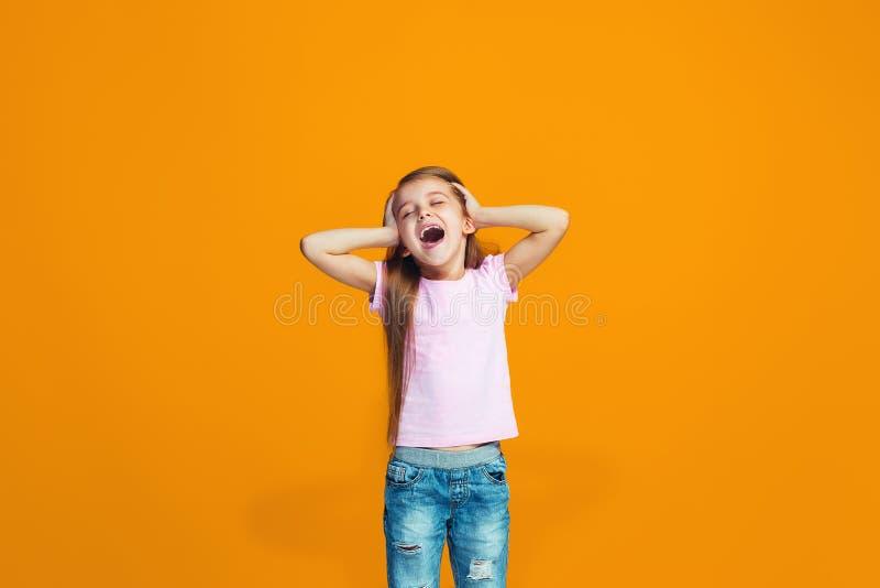 Det lyckliga tonåriga flickaanseendet och le mot orange bakgrund arkivbilder