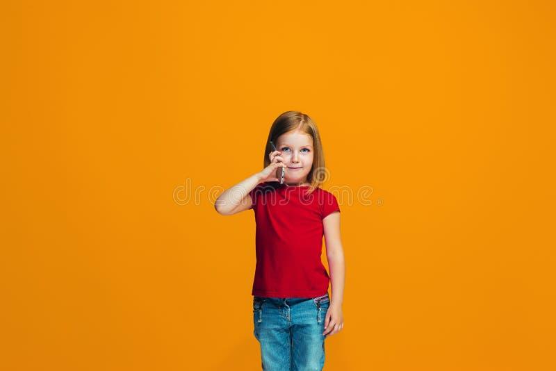 Det lyckliga tonåriga flickaanseendet och le mot orange bakgrund arkivbild