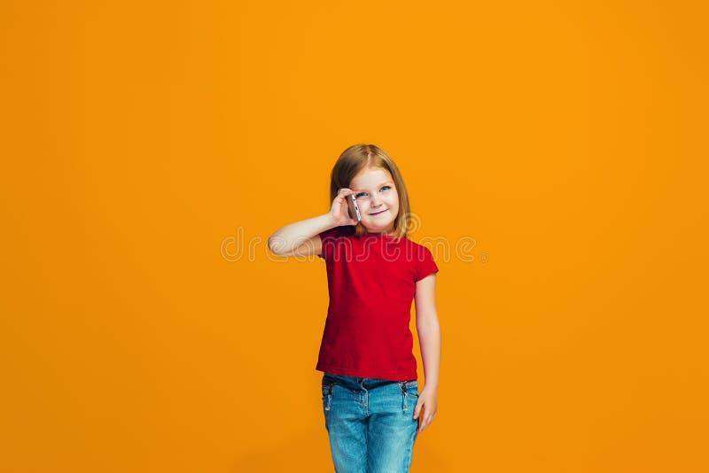 Det lyckliga tonåriga flickaanseendet och le mot orange bakgrund royaltyfri bild