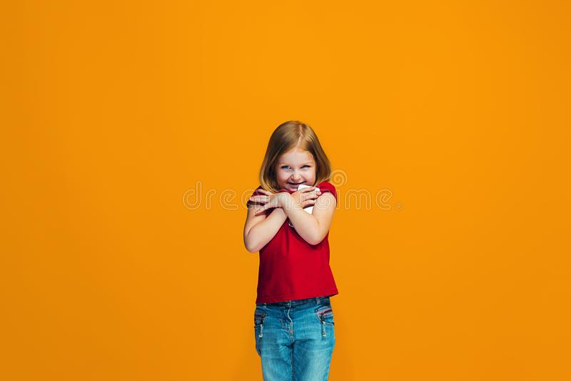 Det lyckliga tonåriga flickaanseendet och le mot orange bakgrund fotografering för bildbyråer