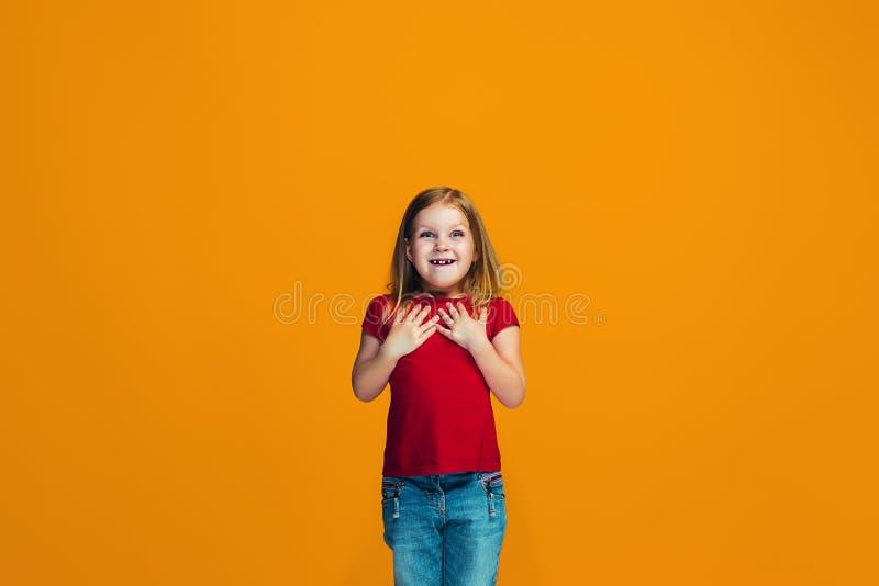 Det lyckliga tonåriga flickaanseendet och le mot orange bakgrund royaltyfri foto