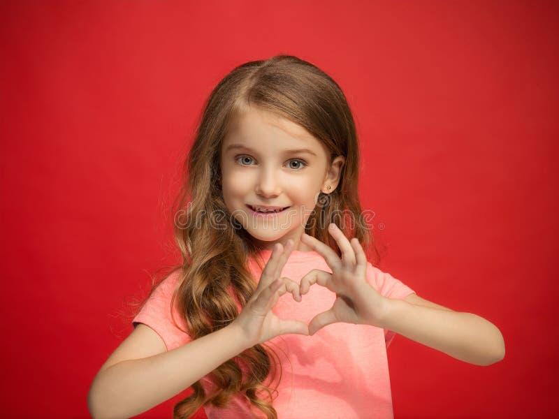 Det lyckliga tonåriga flickaanseendet och le mot röd bakgrund fotografering för bildbyråer