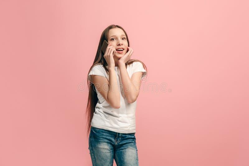 Det lyckliga tonåriga flickaanseendet och le mot rosa bakgrund fotografering för bildbyråer
