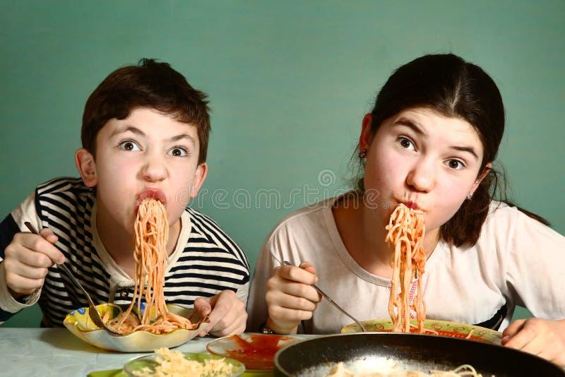 Det lyckliga tonåriga syskonet pojke och flicka äter spagetti royaltyfri bild