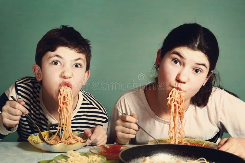 Det lyckliga tonåriga syskonet pojke och flicka äter spagetti arkivbild