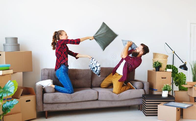 Det lyckliga unga gifta paret flyttar sig till den nya lägenheten, och skratta, kudde hoppet, kamp arkivbilder