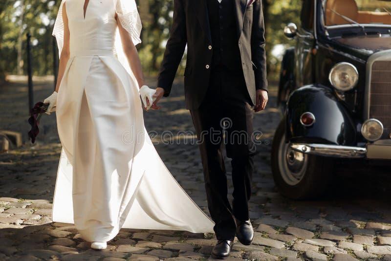 Det lyxiga eleganta bröllopparet som går och rymmer, räcker tätt upp arkivbilder