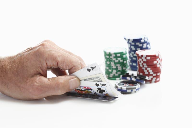 Det mänskliga handinnehavet som spelar kort med dobbleri, gå i flisor royaltyfria foton