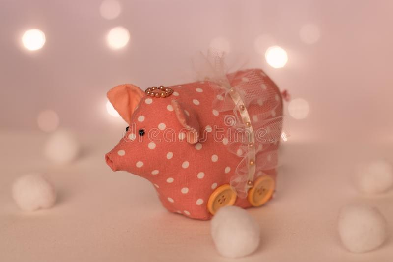 Det mörka rosa svinet med en kjol och en handgjord krans står mot bakgrunden av ljus för det nya året och mjuka bollar arkivbild