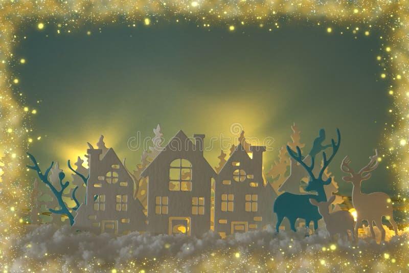 Det magiska landskapet för bakgrund för vintern för julpapperssnittet med hus, träd, hjortar och den insnöade framdelen av guld t arkivbild